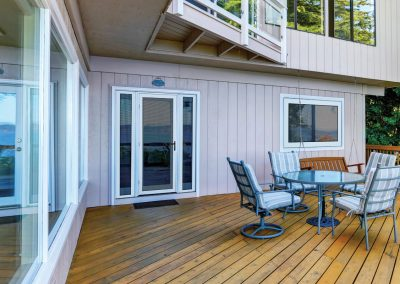 Wooden walkout deck with outdoor table set and swinging bench